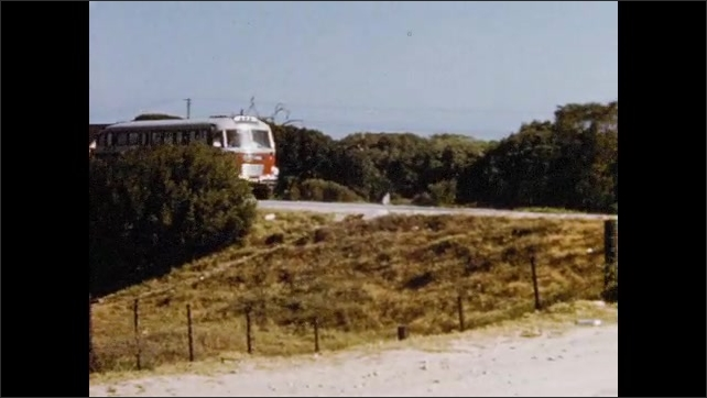 1950s: Bus drives down road.