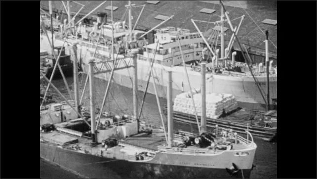1940s: Boats.  Men unload cargo.