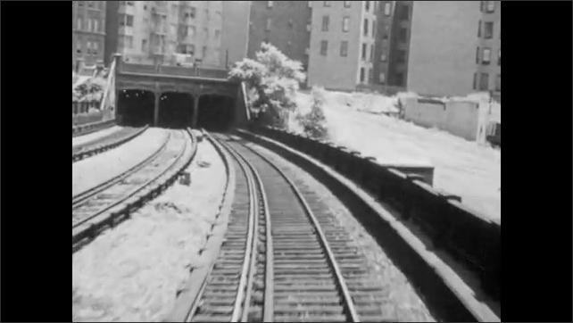 1940s: City.  Elevated train goes into tunnel.
