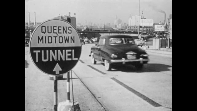 """1940s: Sign reads """"QUEENS MIDTOWN TUNNEL.""""  City.  Cars drive down road."""
