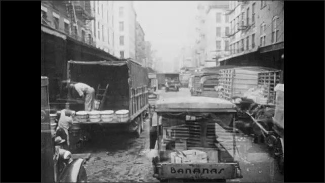 1940s: Trucks drive down street.  Men unload trucks of food.