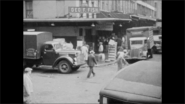1940s: City.  Busy street corner.  Men unload trucks.