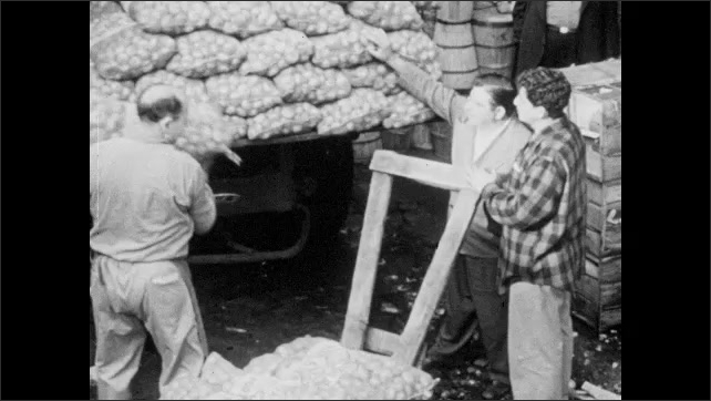 1940s: Men carrying, stacking and pushing crates of food. Man unloads bags of food from back of truck. Crates of food being loaded and unloaded from trucks in lot.