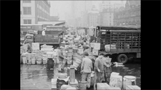 1940s: Man rolls barrel to truck in lot filled with crates and goods. Men load crate onto back of truck. Crates and barrels being loaded and unloaded from trucks. People walking down street.