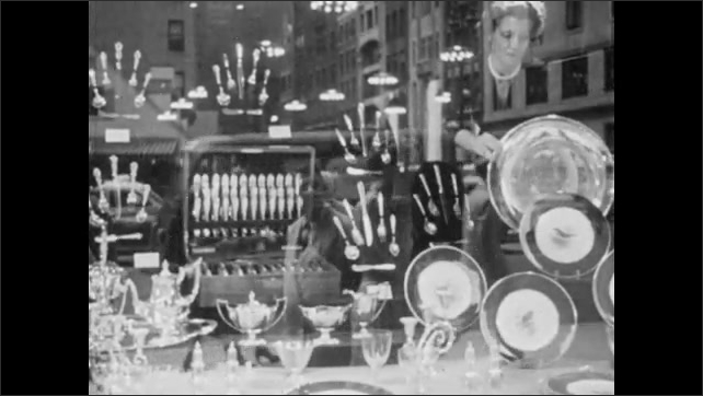 1940s: Woman works on window display of dishware and cutlery. Woman approaches window display of crystal dishware. Crystal dishware on display.