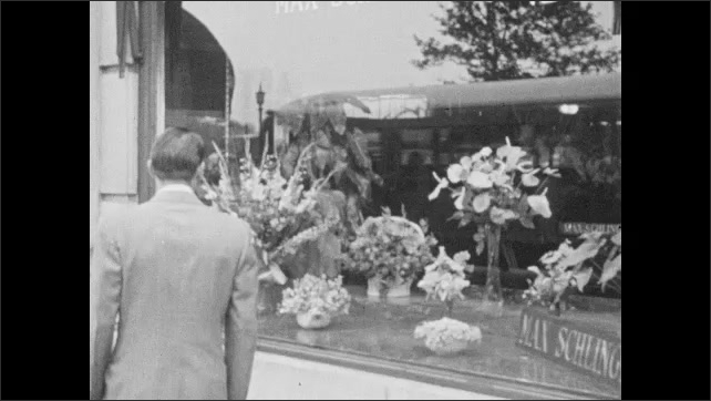 1940s: Man and boy stand in front of window display of model sailboats. Man approaches window display of flowers. Flowers in window display. Man looks at display then walks away.