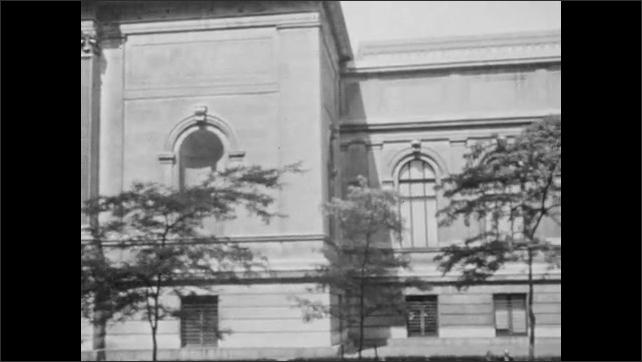 1940s: Cars driving down city street. Exterior of the Metropolitan Museum of Art.