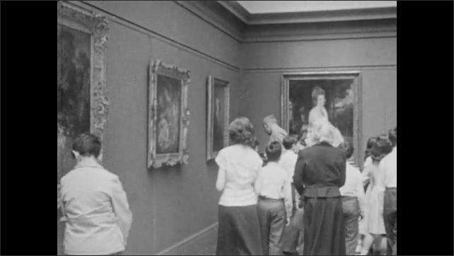 1940s: Painting in Metropolitan Museum of Art. People looking at paintings in museum. Painting. Three people looking at bust of woman.