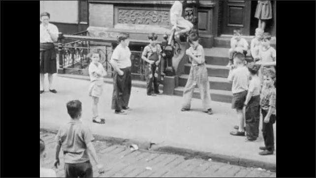 1940s: Children playing stick ball on city street. Children playing with ball in street.