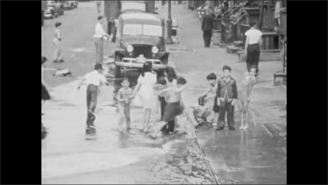 1940s: Children playing with water spewing from fire hydrant on street.
