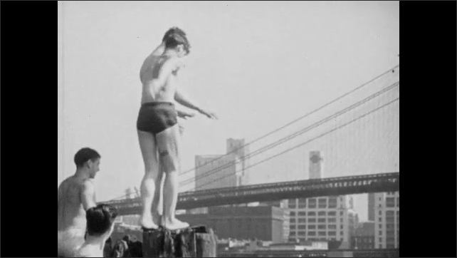 1940s: Boys jump off dock into river in Manhattan.