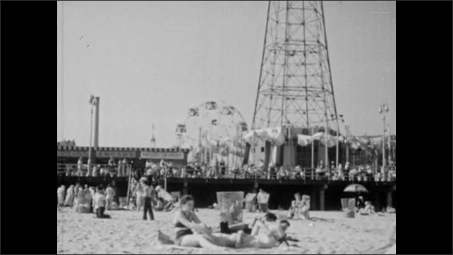1940s: Coney Island. People on beach at Coney Island. Child on beach. Family sitting on bench.