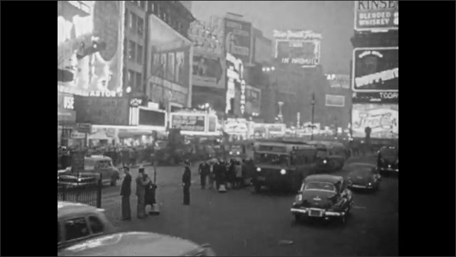 1940s: People on beach at Coney Island. Cars driving through Time Square at night. People walking along sidewalk through Time Square.