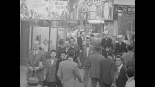 1940s: People walking down Manhattan sidewalk at night. People walking around Time Square at night.