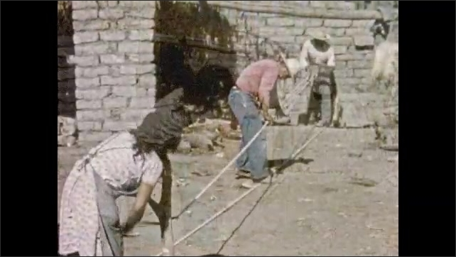 Mexico 1950s: Man holds board, moves board in circle, turns strands of rope. Woman turns crank at other end of rope. Man stands in middle and guides strands of rope.
