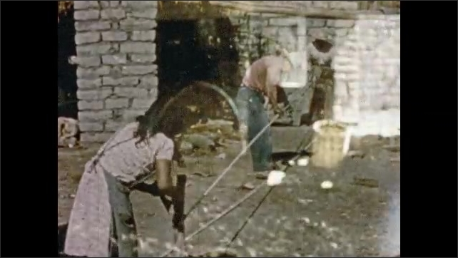 Mexico 1950s: Man pulls string out of agave plant. Man washes hands in bowl of soapy water. Woman and man spin rope. Man guides donkey around in circle to turn millstone in mill. Agave plant.