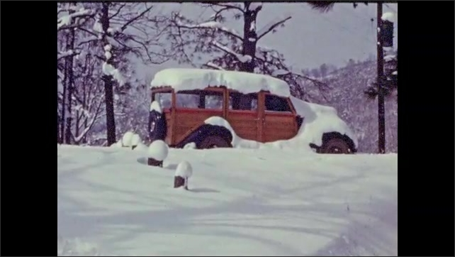 1940s: Snow covers car near woods. Snow falls on car in mountain area.