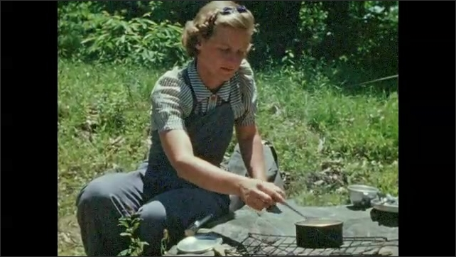 1940s: Woman stirs pot over campfire. Woman sits under lean to at campsite.