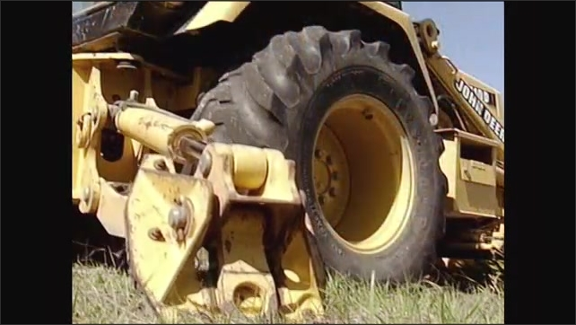 2000s: Stabilizers lowering on excavator. Low angle, stabilizer lowering, wheel of excavator lifts.