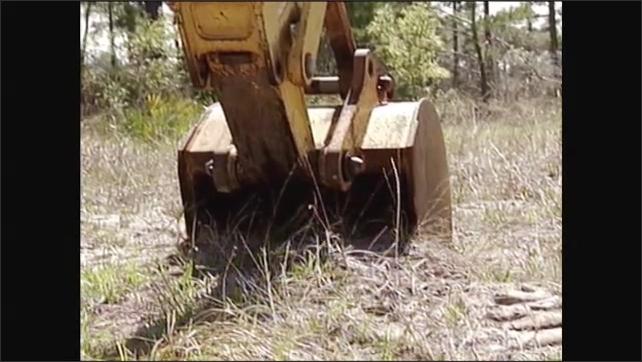 2000s: Man operating excavator. Excavator bucket digging into soil. Bucket lifting soil.