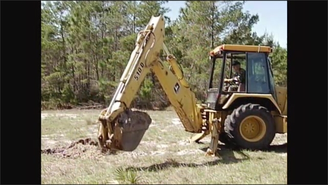 2000s: Excavator digging in soil. Front view, excavator bucket swings to side. Excavator dumps soil.