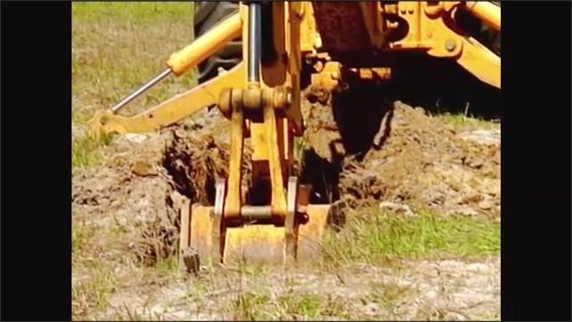 2000s: Front of excavator, bucket swings to front. Bucket digging in soil.