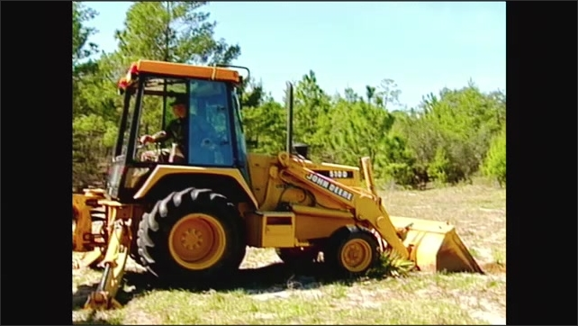 2000s: Front view of excavator. Man operating excavator, looks around. Excavator bucket lifting.