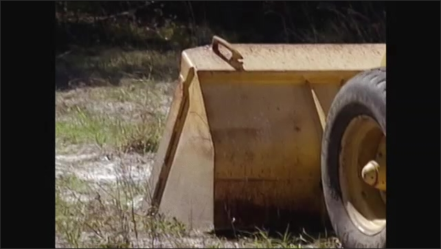 2000s: Man sets rope and chain by pipe on ground. Excavator reversing. Bucket lowering. Stabilizer leg lowering.