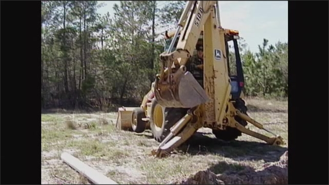 2000s: Man operating excavator, boom lifting. Front view of excavator, bucket swings to side, lowers toward pipe.