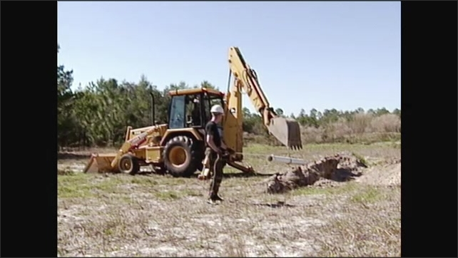 2000s: Excavator lifting pipe, man holds rope tied to pipe. Excavator lowers pipe into hole.