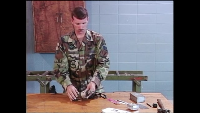 2000s: Man in army fatigues tightens head of power drill with bit in it then lays power drill down. Power drill spins with bit off alignment.
