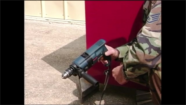 2000s: Man in army fatigues kneeling on ground inspects power drill in hands. Man flips action switch on top of drill.