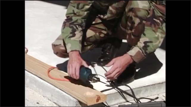 2000s: After drilling hole in wood plank, man in army fatigues lays drill down then begins loosening drill head.