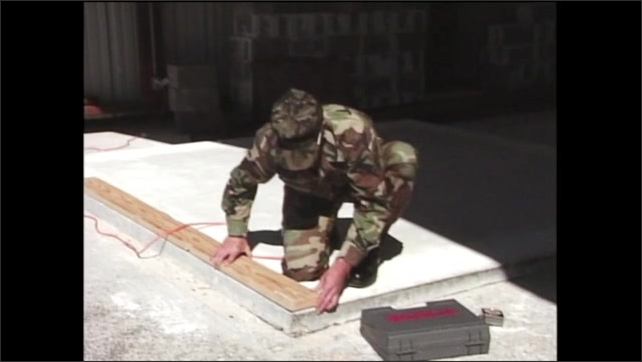 2000s: Wood board with hole in it lays on top of concrete slab with hole in it. Man in army fatigue kneeling on ground lines up hole in wood with hole in concrete.