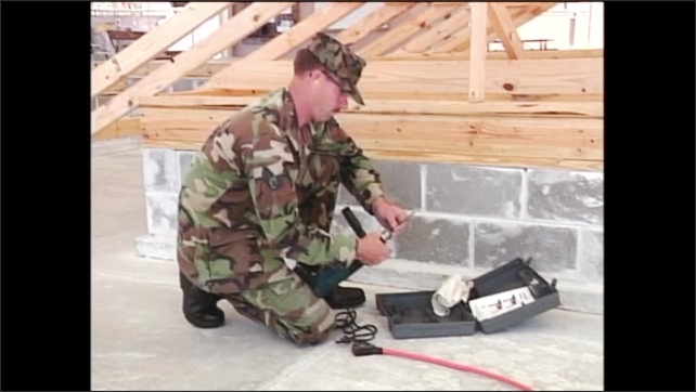 2000s: Man in army fatigues kneeling on ground puts drill bit in head of power drill and tightens it with key.