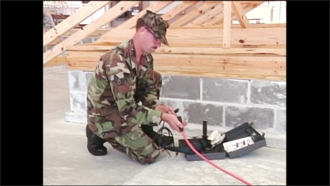 2000s: Man in army fatigues kneeling on ground checks over power drill and plugs it into extension cord. Drill bit lines up with concrete.