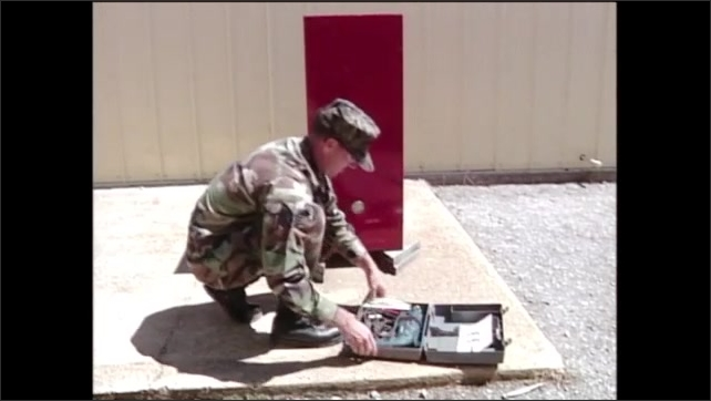 2000s: Man in army fatigues kneels on ground with toolbox, opens toolbox with power drill inside. Man measures metal box next to him and makes mark on it.