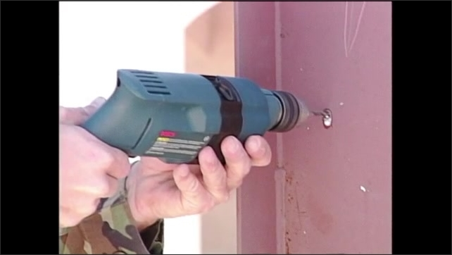 2000s: Man in army fatigues drills hole in side of metal casing. Man drills hole in tube on ground.