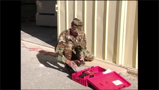 2000s: Man in army fatigues lays toolbox with hammer drill inside on ground, opens box and takes out drill.