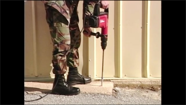 2000s: Man in army fatigues holds hammer drill while drilling hole in concrete ground.