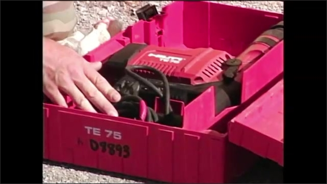 2000s: Man in army fatigues kneeling on ground, holds hammer drill, folds up handle and puts drill in toolbox and closes lid.