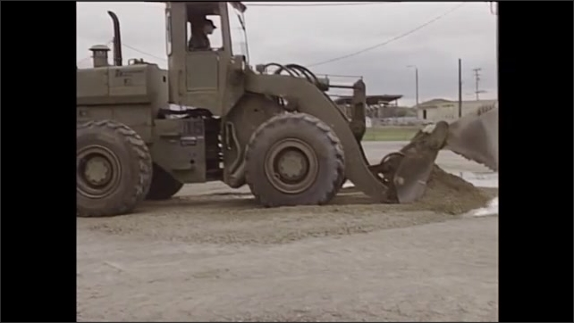 2000s: Man uses front end loader to level dirt lot.