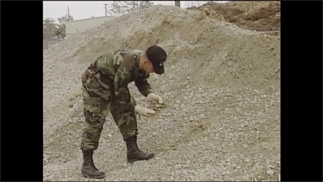 2000s: Man drives front end loader.  Man approaches stockpile and picks up material.  Man examines handful of dirt and gravel.