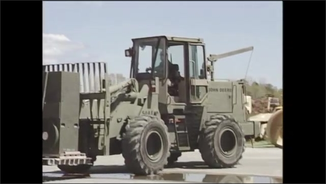 2000s: forklift forks and wheels move forward, soldier in camouflage drives forklift with equipment