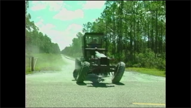 2000s: Man drives construction grader from rural dirt road onto highway.
