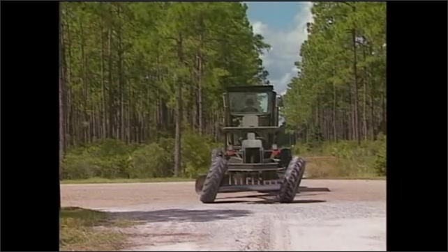 2000s: Man drives construction grader from highway to rural dirt road. Tires on grader straighten and straddle windrow.