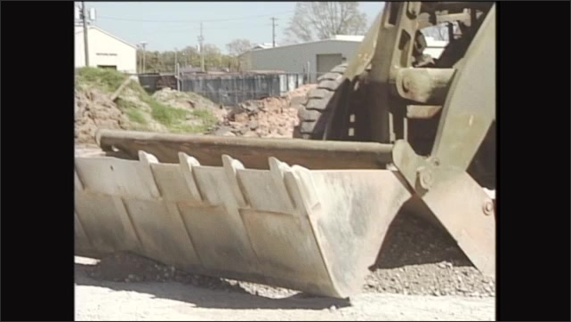 2000s: Man drives front end loader, scoops dirt into dump truck.
