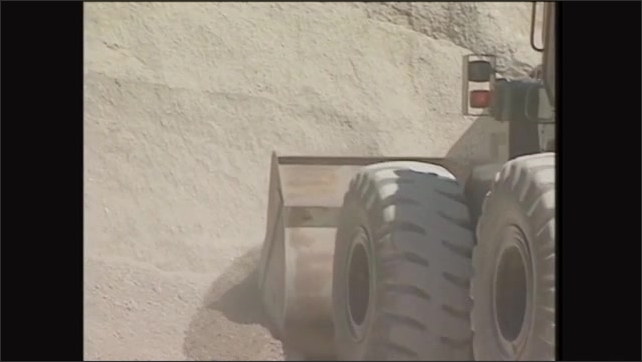 2000s: Man drives front end loader towards pile of dirt, bucket scoops dirt. Pile of gravel.