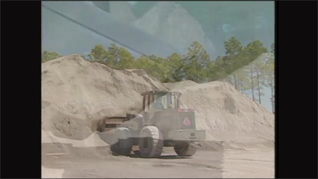 2000s: 2000s: Man drives front end loader towards pile of dirt, scoops dirt. Man reverses away from pile.