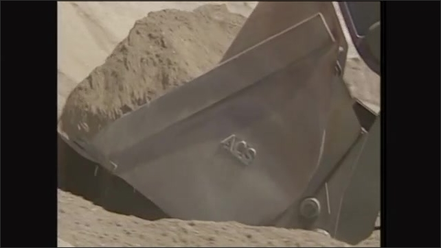 2000s: Man operates front end loader, scoops dirt from pile.